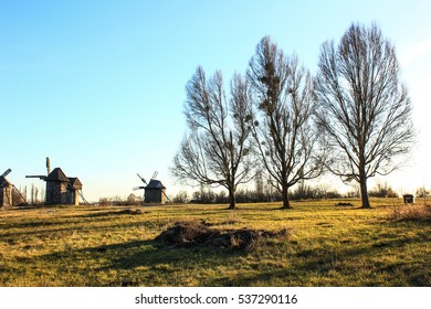 Old wooden windmill in the countryside. autumn landscape. three poplar