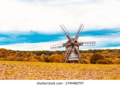 Old wooden windmill on the field near the forest under the blue sky. Traditional vintage historical building rural.  Travel place for tourism in Ukraine.