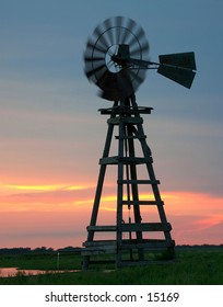 An old wooden windmill at sunset
