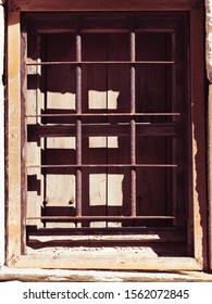 Old wooden window with chutters and metal grilles in old stone wall made building home.