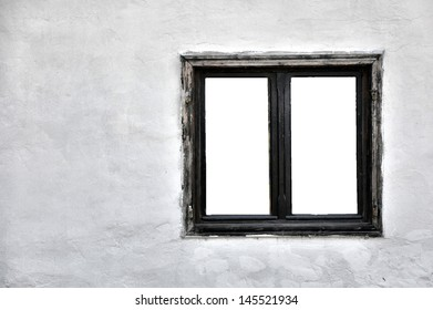Old wooden window with cutout panes on a grungy white wall.