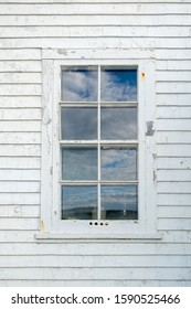 An old wooden window with eight panes of glass in an exterior wall of a white wood clapboard wall. There are reflections of blue sky and clouds in the glass. The wall is worn and paint is peeling.