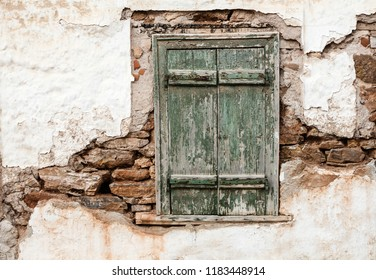 Old wooden window with green shutters on weathered wall.