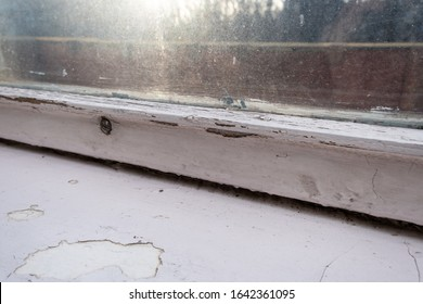 Old wooden window with peeling paint and durt needed to be repaired or replaced.