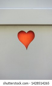 Old wooden window shutter blinder heart shape cut orange close up