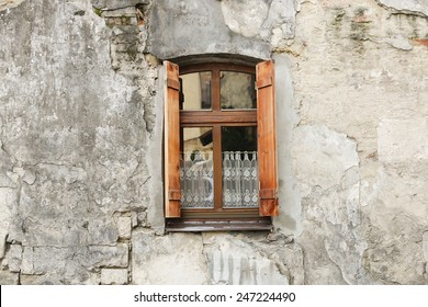 old wooden window with shutters and lace curtains.