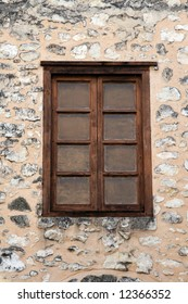 An old wooden window in a stone building wall.