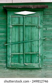 Old wooden window in a wall painte in green color. Astrakhan, Russia.