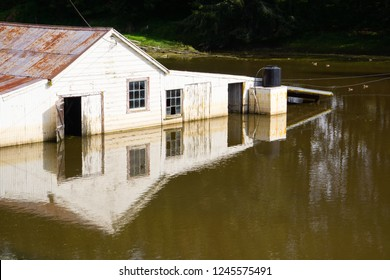 An old wooden wool shed, farm building surrounded by flood water is reflected in the water on a farm in Taihape, North Island, New Zealand.