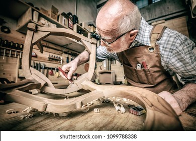 old woodworker at work in workshop