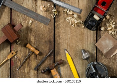 Old woodworking tools. Tools include a bradle, punch, hammer, gauge, ruler, drill and drill bit an auger, chisel, pencil and wood plane