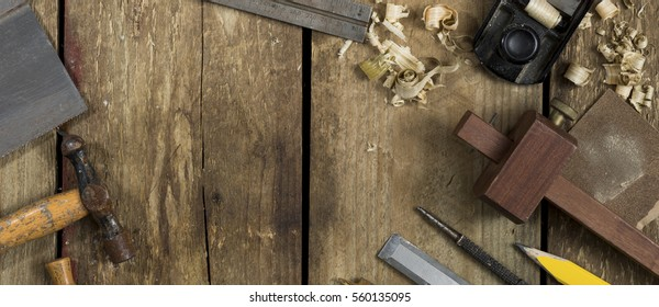 Old woodworking tools shot in website banner format. Tools include a bradle, punch, gauge, ruler, drill and drill bit an auger and wood plane