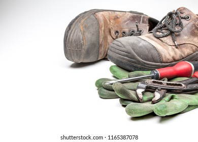 old work shoes with iron tips, new and old work gloves with a cross-screwdriver and a water wrench