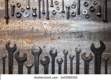Old work tools and screws on rusty metal table. Top view variation of vintage wrenches and dirty bolt and nut fastener. Flat lay with copy space