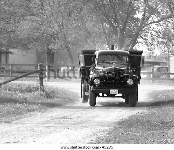 Old work truck kicking up dust while driving up a gravel road way
