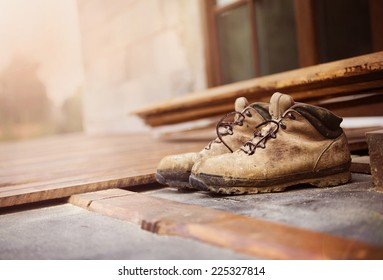 Old worker boots left on unfinished patio wooden flooring