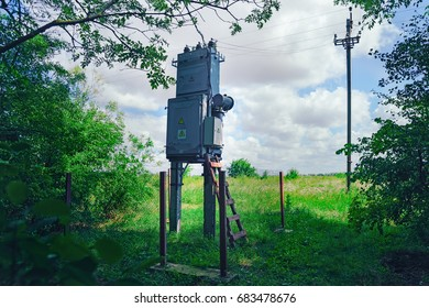 Old working rural electrical distribution transformer in the forest. Sunny day, the concept of industrial, forest landscape.