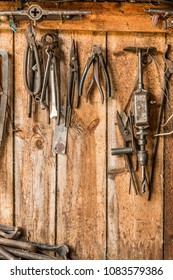 old working tool on the background of wooden panels, the tools of the artisan hang on nails, the historical industry background