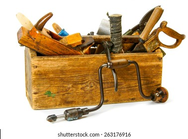 Old working tools. Working tools (drill, axe, saw and others) in an old box on white background.