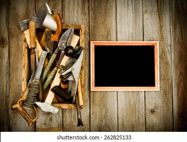 Old working tools. Frame with old tools (scissors, pliers, saw and others) in a box on a wooden background.