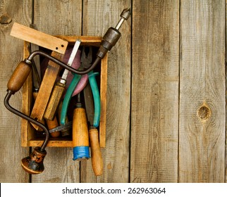 Old working tools. Old working tools (saw, axe, plane and others) in a box on a wooden background.
