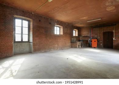 Vieux atelier intérieur avec murs et fenêtres en briques, lumière du soleil