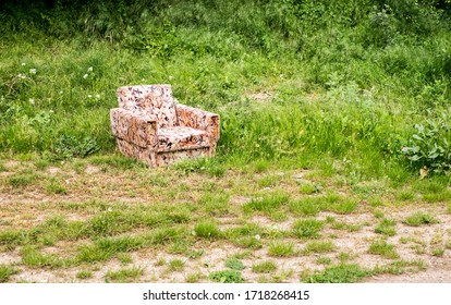 Old worn armchair sitting abandoned in grass