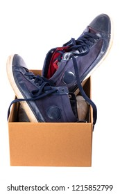 Old worn blue shoes, stuck in a cardboard box. Isolated on white background.