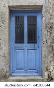 Old and worn blue wooden door with glass and ironwork in Les Baux