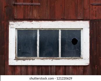 Old, worn, broken window on red wooden house
