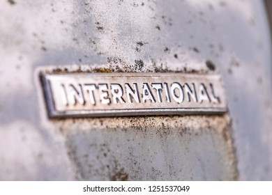 "Old worn chrome plate with engraving ""INTERNATIONAL"" on it. Plate on a rusty metal surface with spots of mold and moss on it."