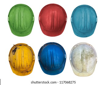 Old and worn colorful construction helmets isolated on white