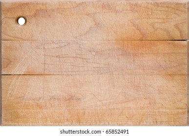 Old worn, cracked and scratched wooden cutting board.