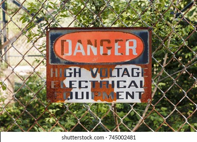Old and worn Danger High Voltage sigh on a chain link fence.