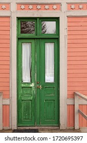 an old worn green wooden door to a pink house
