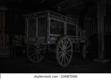 Old and worn horse carriage in hears model from the late 1800s, with glass windows and curtains in a dark and spooky environment