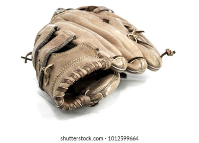 Old worn leather baseball glove on a wooden table background