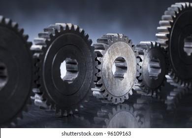 Old worn metallic cog gear wheels, with one gear in spotlight.