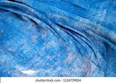 Old, worn out blue tarpaulin laid out with a few folds.
