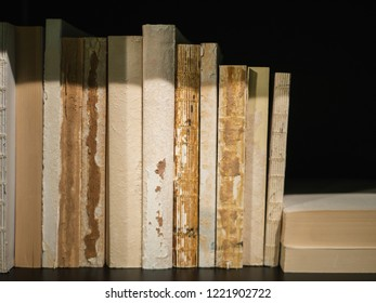 Old, worn out books standing on a black book shelf