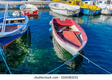 Old worn out traditional wooden fishing boat moored at a dock or a pier above clear blue and turquoise transparent sea water with the boat reflection, Croatia