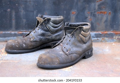 Old worn out work shoes  against a brown rusty background