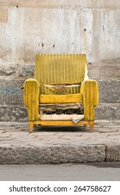 Old worn out yellow chair against a stone wall