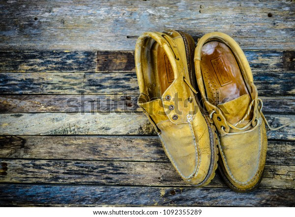 Old worn pair of rawhide leather men's shoes presented on weathered wooden table top.