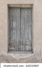 Old worn pale blue wooden stutters or blinds closed in medieval house in Les Baux, France on a sunny summer day.