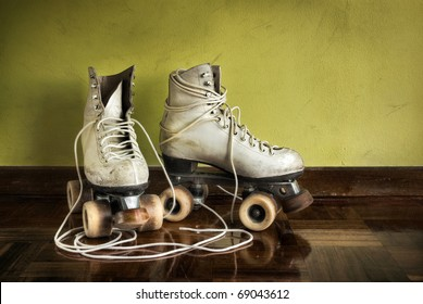 Old worn roller skates with big shoe-laces on a yellow wall background