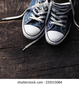 Old worn sneakers on a background of boards
