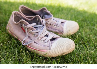 Old worn sneakers on green grass