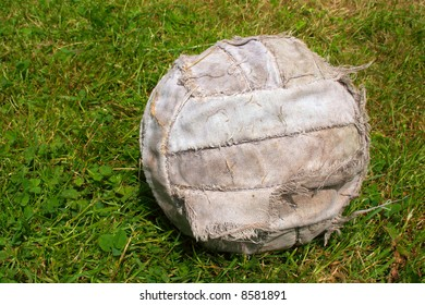 An old worn soccer football ball on grass football field with copy space on the left