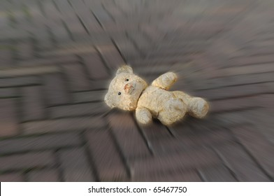 Old worn teddy bear lost on the street